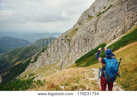 Young man in hiking gear taking photos of the landscape from a trail high up in a rugged mountain range