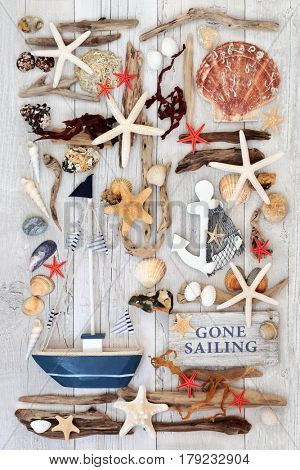 Sailing themed seaside abstract with decorative rustic wooden boat and sign with seashells, driftwood, seaweed and rocks on distressed white wood background.