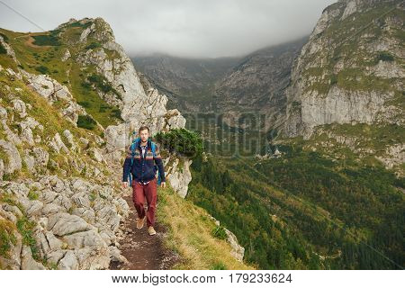 Portrait of a young man wearing hiking gear wearing a backpack walking alone along a rocky trail in the mountains on an overcast day