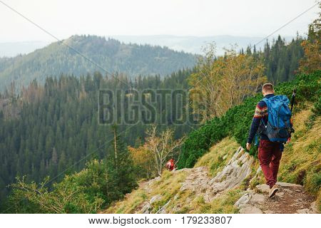 Rearview of two young men in hiking gear wearing backpacks walking together along a trail high up in the hills