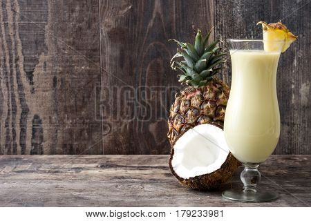 Piña colada cocktail on wooden table background.