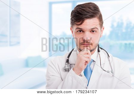 Portrait Of Handsome Pensive Doctor In White Coat