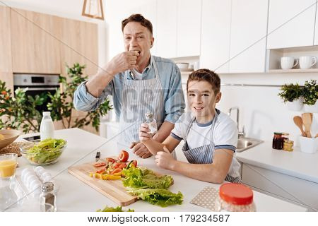 Great taste. Positive delighted son and his father cooking together and tasting vegetables while expressing gladness