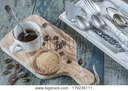 Black coffee in vintage coffee cup with a silver teaspoon spilled coffee beans and cane sugar in a wooden bowl on the old wooden table