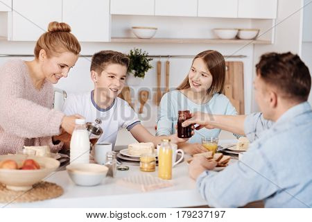 Take it. Pleasant loving father passing jam to his son while sitting at the table and enjoying breakfast with the whole family