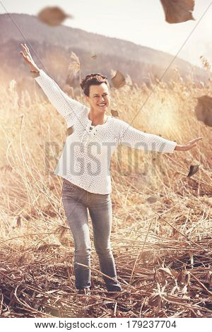 Casual woman mid-fifties happy in the autumn when the sun shines in the field of reeds.