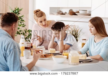 How you can do that. Angry emotional parents yelling at their son while teaching him how to behave while sitting in the kitchen