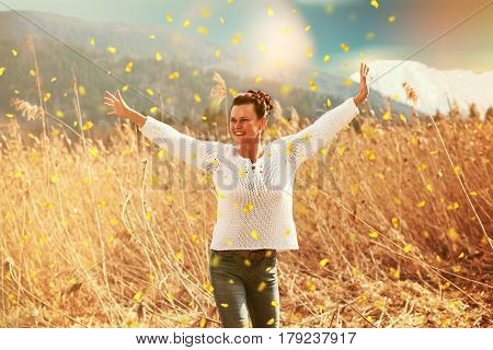 woman to the fifty stands with joy in the spring sunshine in the reed field during flying flowers and snow-covered mountains in the background