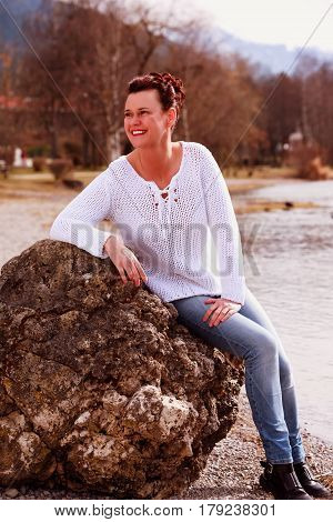 Fashionable older woman sitting on the lake shore