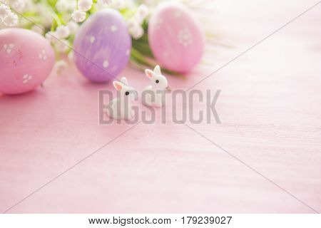 Easter Eggs And Flowers With Bunny Statuettes On Wooden Background. Happy Easter
