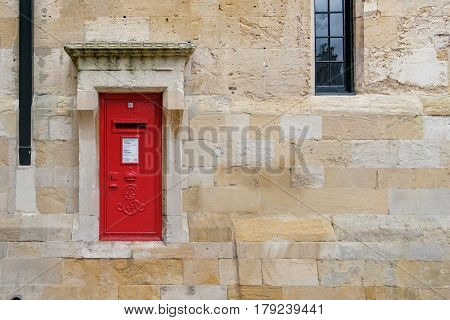 WINDSOR UK - MARCH 18: A traditional iconic British post box in a stone wall in March 2017.