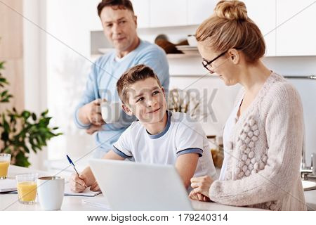 Good result. Positive diligent boy sitting at the table and doing his home work while his mother feeling ptoud of him