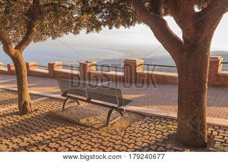 Gargano promontory: panoramic view from Monte Sant'Angelo, on background Adriatic coast with the Gulf of Manfredonia (Italy).Relaxing on a bench in the town park.