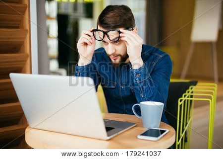 Business Man With Glasses Having Eyesight Problems Confused With Laptop Isolated On Office Backgroun