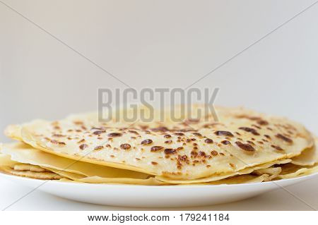 Thin homemade pancakes on white plate. Pile of fresh crepes. Horizontal photo of fried crepes with crispy edges on grey and white background