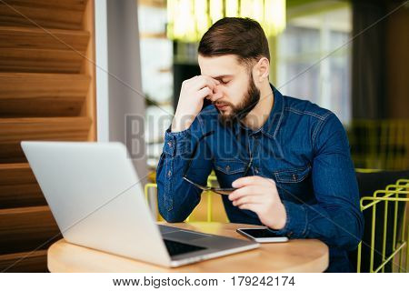 Frustrated Young Beard Man Massaging His Nose And Keeping Eyes Closed While Sitting At His Working P