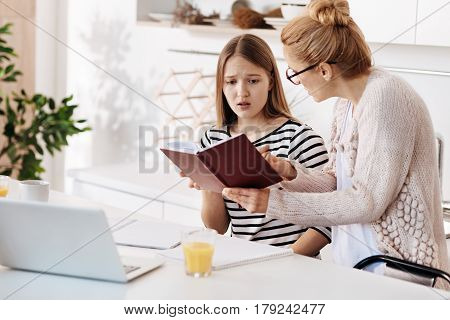 You should study hard. Caring strict mother scolding her daughter for bad marks while sitting together in the kitchen