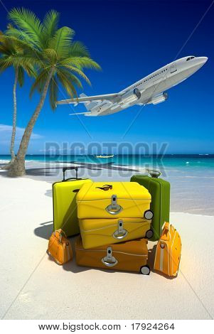 Pile of yellow luggage on a tropical beach and a flying plane