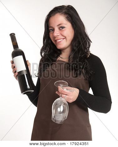 Female with apron presenting a wine bottle with a blank label and a pair of glasses