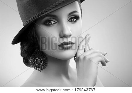 Forever stylish. Black and white close up of a stunning beautiful woman posing elegantly wearing a hat copyspace grace beauty salon makeup retro vintage classic sensual feminine fashion icon concept