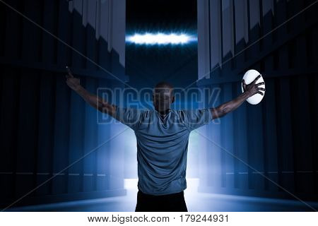 Rear view of sportsman with arms raised holding rugby ball against football pitch with flags and lights 3d