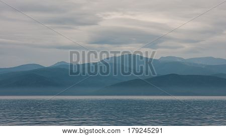 Blurred light blue landscape of hills, clouds and Baikal lake, Russia