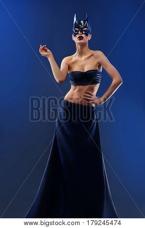 Batgirl. Full length shot of a female fashion model wearing batman mask top and long skirt posing gracefully in studio on blue background femininity vogue icon fashionable style mysterious sexy body