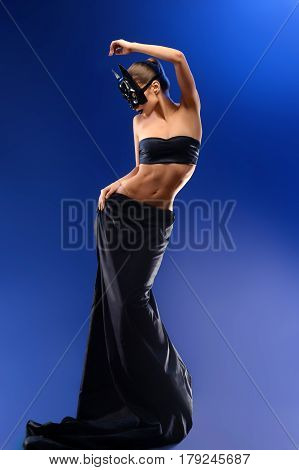 Modeling batgirl. Young fashion female model with perfectly shaped sexy body wearing batman mask posing seductively on blue background fashion modeling lifestyle stylish concept