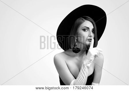 Black and white portrait of a beautiful elegant young fashion model shushing to the camera wearing a hat and gloves posing in a black dress copyspace fashionable stylish luxury beauty concept.