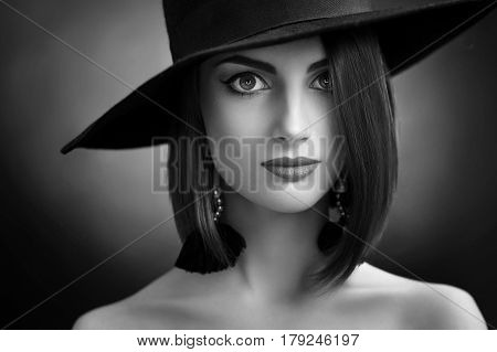 Monochrome studio close up portrait of a sexy young elegant woman posing in a hat on dark background cosmetics skin face lips eyes expressive confident feminine graceful.