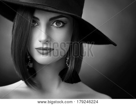 Black and white close up of a beautiful elegant woman wearing a wide hat posing in studio copyspace old fashioned stylish retro vintage outfit fierce beauty cosmetics sexuality seduction.