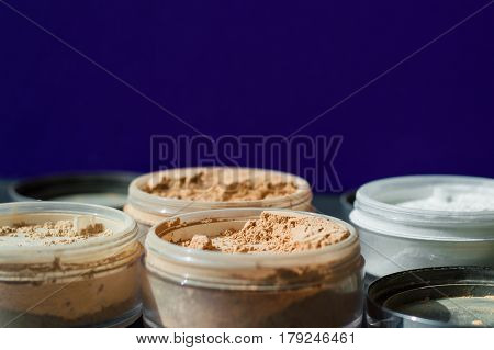 Variety of beauty containers with mineral make-up powder for matt skin on purple background