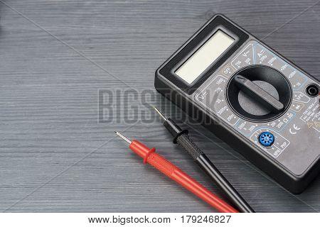 Multimeter on a dark wooden background. appliance, black,