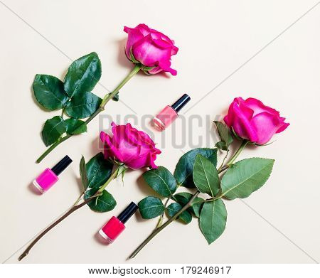 Nail polishes and roses on beige background