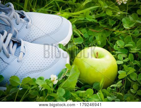 Sports shoes sneakers and apple on fresh green grass. Sports in the open air. Selective focus