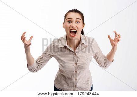 Young beautiful crazy brunette businessgirl screaming in camera over white background