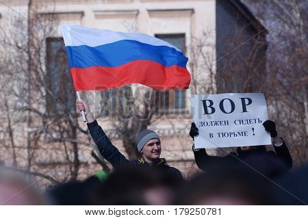 Demonstration against corruption in russia on March 26, 2017. one demonstrator holds the flag of Russia. The second demonstrator holds a poster with the inscription: