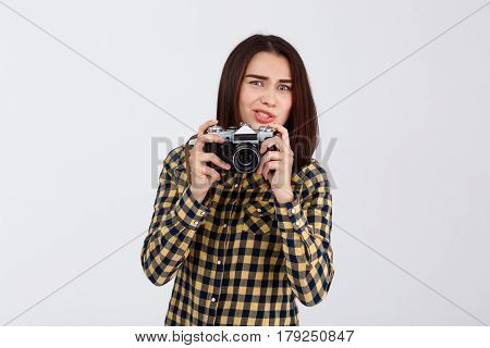 Young beautiful brunette photographer taking pictures, looking at camera over white background.