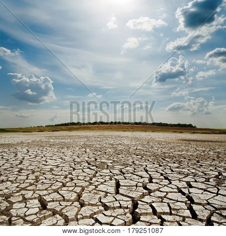 dramatic clouds with sun over drought earth