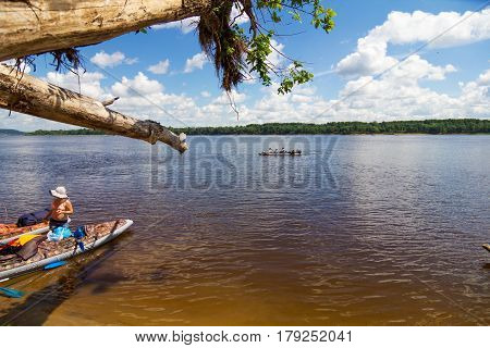 Landscape with canoes on the river. View from the beach