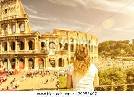 The female tourist looks at the Colosseum in Rome, Italy. The Colosseum (Coliseum) is an important monument of antiquity and is one of the main tourist attractions of Rome.