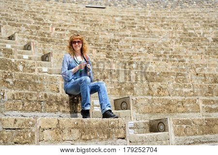 A young female tourist sitting in the ancient amphitheater in Pompeii, Italy. Pompeii is a Roman city died from the eruption of Mount Vesuvius in 79 AD.