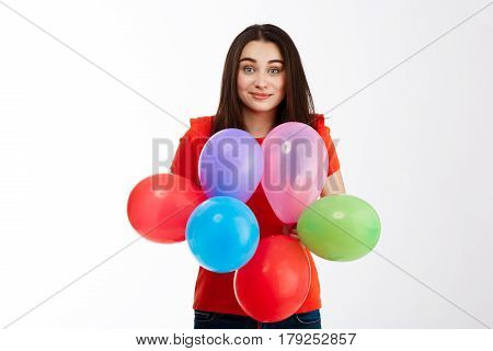 Young beautiful brunette girl dressed in red shirt holding colorful baloons looking at camera smiling over white background