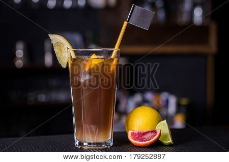 Cocktail with cola and fruit on the bar counter