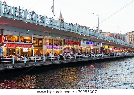 ISTANBUL - MAY 24, 2013: Tourists relax in the restaurants located on the first level of the famous Galata Bridge in Istanbul, Turkey. The Galata Bridge is one of the main attractions of Istanbul.
