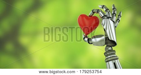 3d image of robot hand holding red heard shape decoration against trees in forest