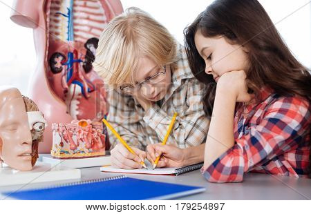 Do not miss a number. Determined hard working bright classmates doing their home assignment together while sitting at the table spending time in school laboratory