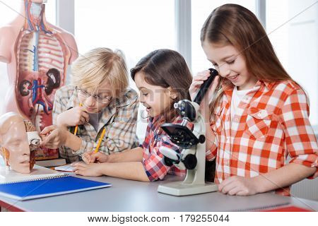 Having fun together. Diligent motivated intelligent kids conducting a research together while a girl looking in the microscope and her friends examining a brain model