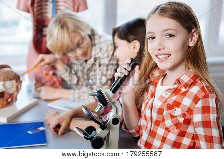 A new generation. Diligent attentive young scholars examining some bacteria using microscope while spending biology class in a lab