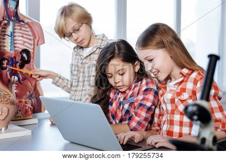 Running a double check. Analytical incredible smart children reading a book on the laptop and comparing pictures in it with in class human model